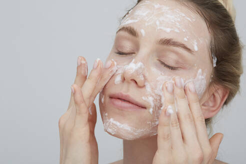 Portrait of blond young woman with eyes closed applying cream on her face - PGCF00029
