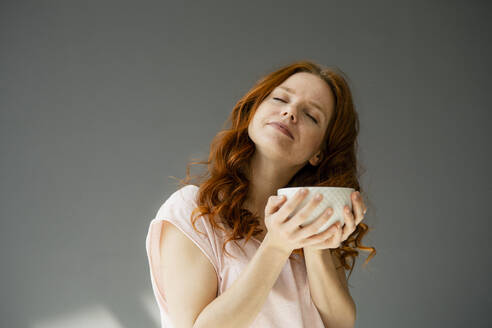 Portrait of relaxed redheaded woman with cereal bowl against grey background - KNSF06490