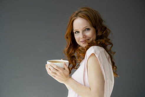 Portrait of smiling redheaded woman with coffee bowl against grey background - KNSF06493