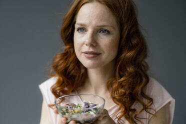 Portrait of redheaded woman with glass bowl of blossoms - KNSF06499