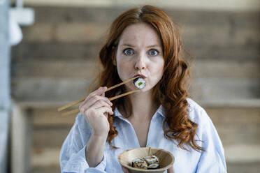 Portrait of redheaded woman eating sushi - KNSF06511