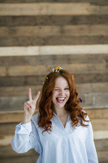 Portrait of redheaded woman flowers in hair showing victory sign - KNSF06514
