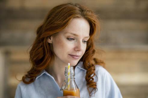 Portrait of redheaded woman   drinking juice - KNSF06523