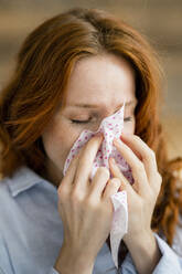 Redheaded woman blowing nose - KNSF06529