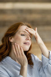 Portrait of redheaded woman touching her face - KNSF06532