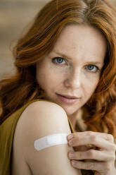 Portrait of redheaded woman with band-aid on her shoulder - KNSF06535