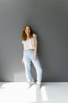 Portrait of laughing redheaded woman standing in front of grey wall - KNSF06544