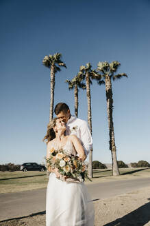 Happy bride and groom hugging at palm trees under blue sky - LHPF00789