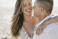 Happy affectionate bride and groom hugging outdoors - LHPF00798