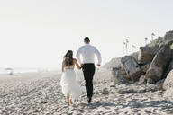 Rear view of bride and groom running on the beach - LHPF00804