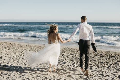 Rear view of bride and groom running on the beach - LHPF00810