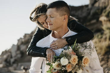 Affectionate bride embracing groom at the coast - LHPF00813