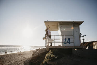 Bride and groom at lifeguard hut on the beach at sunset - LHPF00816