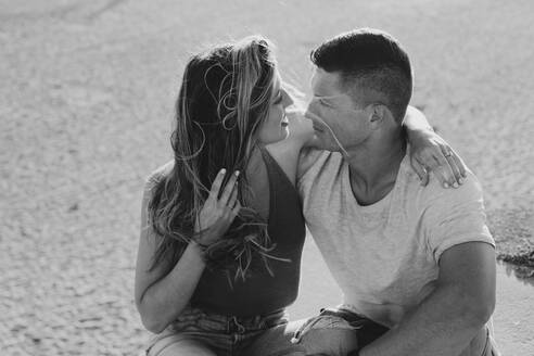 Affectionate young couple sitting on the beach - LHPF00825