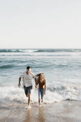 Happy young couple running at the seashore - LHPF00831