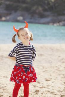 Portrait of girl standing on the beach wearing devil's horns - XCF00203