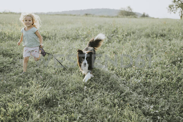 Girl running with dog on a meadow in the countryside - DWF00492 - Frederik Franz/Westend61