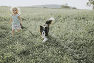 Girl running with dog on a meadow in the countryside - DWF00492