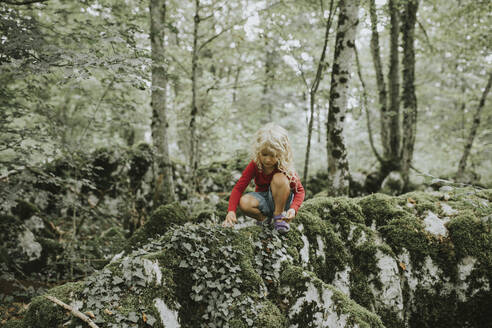 Blond girl sitting on rock in the forest - DWF00495
