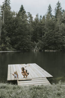 Mother and daughter crouching on jetty at a lake - DWF00501