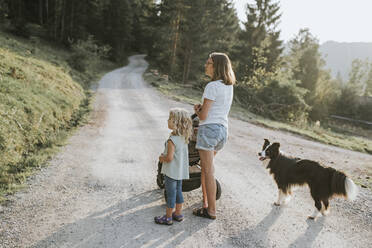 Mother with daughter, stroller and dog standing on forest path - DWF00507