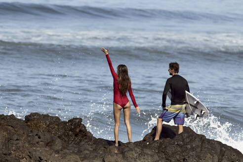 Rear view of a couple standing at the rocky beach, man with surfboard - KNTF03406