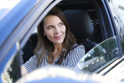 Portrait of smiling woman driving car - PNEF01984