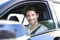 Portrait of smiling man driving car - PNEF01987