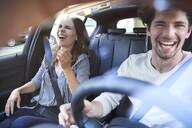 Laughing couple in a car with man driving - PNEF01990