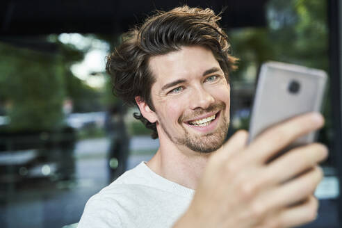Portrait of happy man holding cell phone in the city - PNEF02029
