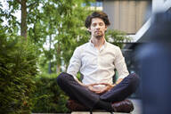 Businessman doing yoga on a bench in the city - PNEF02035