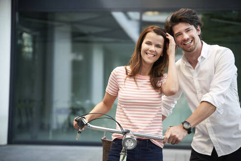 Portrait of happy couple with bicycle in the city - PNEF02047