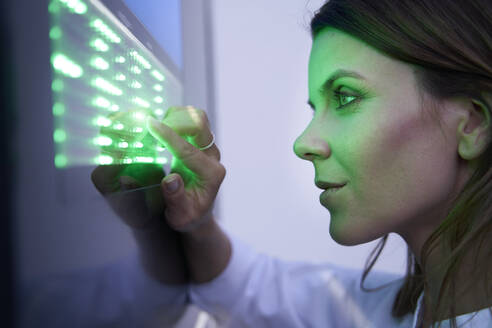 Close-up of woman touching green led touchscreen - PNEF02077