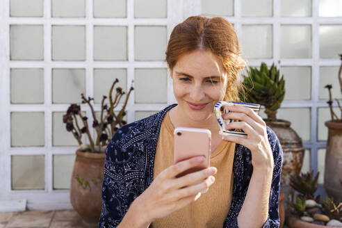 Portrait of smiling redheaded young woman with cup of coffee on terrace looking at cell phone - AFVF03953
