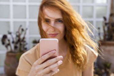 Hand of smiling redheaded young woman holding cell phone, close-up - AFVF03956