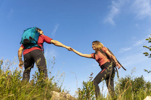 Young couple hiking in mountain meadow - MCVF00011