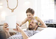 Happy young couple with tablet in living room at home - MJFKF00003