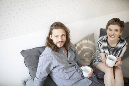 Portrait of happy young couple in pyjamas on bed couch at home - MJFKF00015