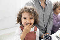 Portrait of playful boy with his family eating blueberries at table - MJFKF00021