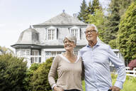 Smiling senior couple standing in garden of their home - MJFKF00030