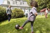 Happy extended family playing football in garden - MJFKF00036
