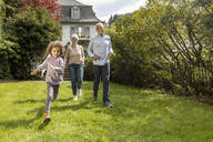 Happy grandson with grandparents running in garden - MJFKF00042