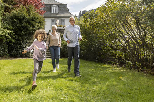 Happy grandson with grandparents running in garden - MJFKF00042