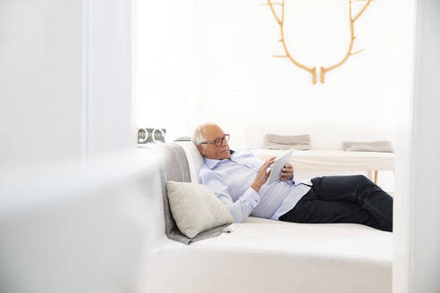 Senior man lying on couch at home using tablet - MJFKF00057