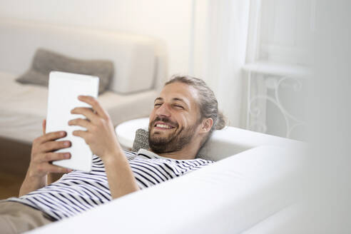 Smiling young man lying on couch at home using tablet - MJFKF00063