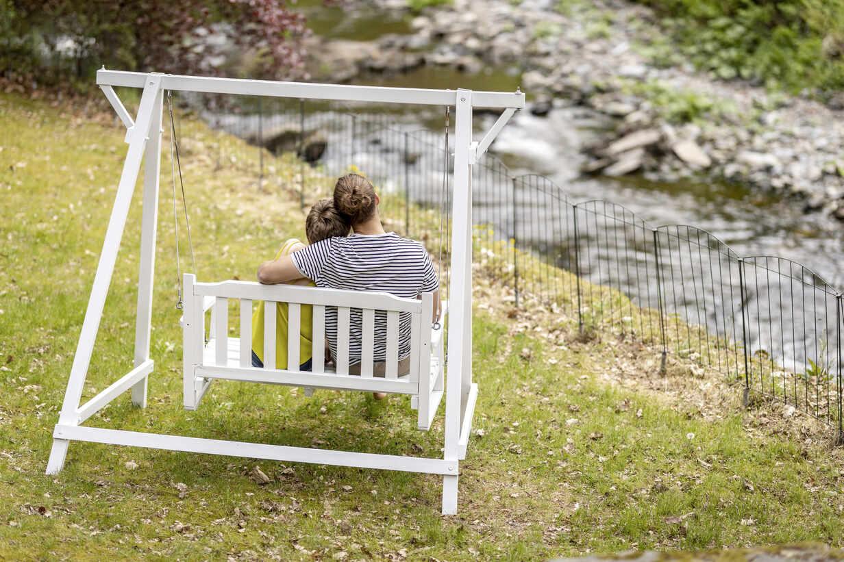 Rear view of smiling sitting on canopy swing in garden - MJFKF00069 - MiJo/Westend61