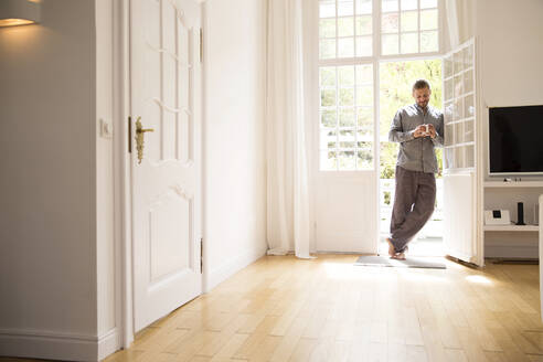 Young man in pyjama standing at the terrace door at home - MJFKF00090