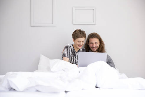 Young couple with laptop in bed at home - MJFKF00096