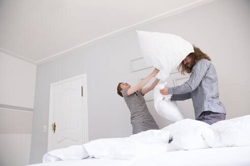 Playful young couple having a pillow fight at home - MJFKF00099