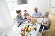 Happy senior couple with adult children having lunch at home - MJFKF00120